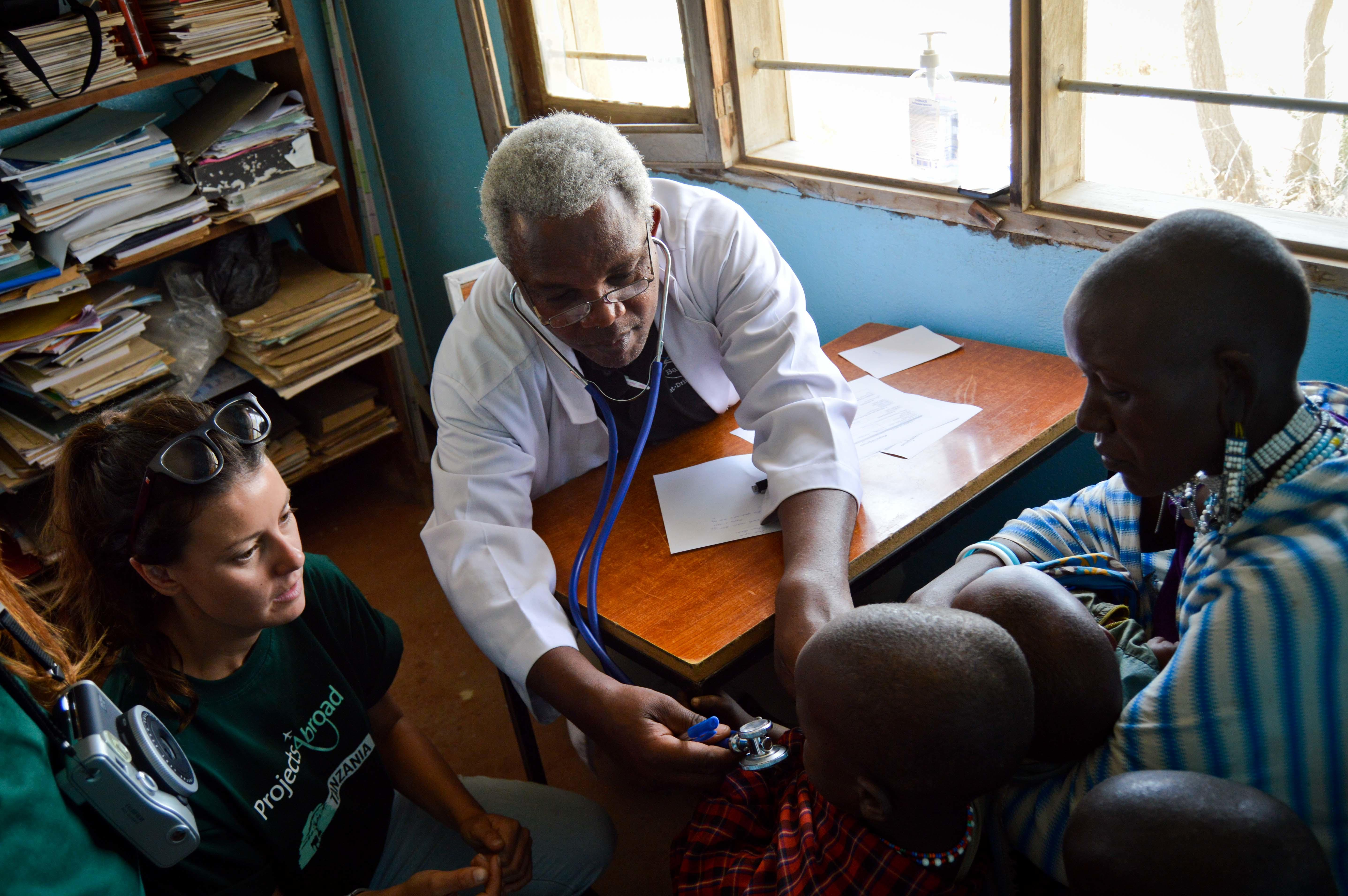 A student doing a Dentistry internship in Tanzania observes a local doctor as he performs a health check for a child.